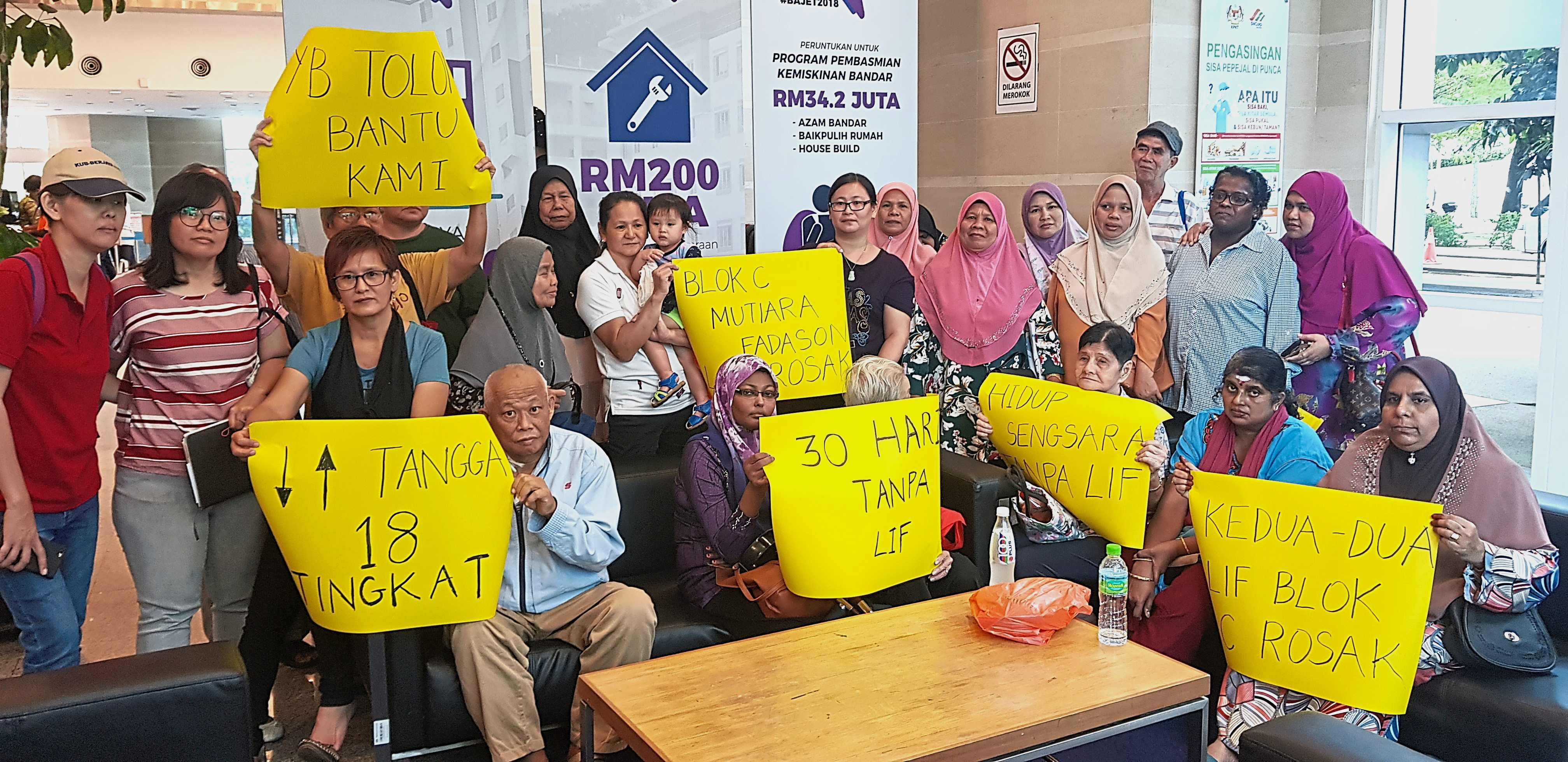 Block C Mutiara Fadason residents showing placards explaining their predicament after being forced to use the stairs for about a month.