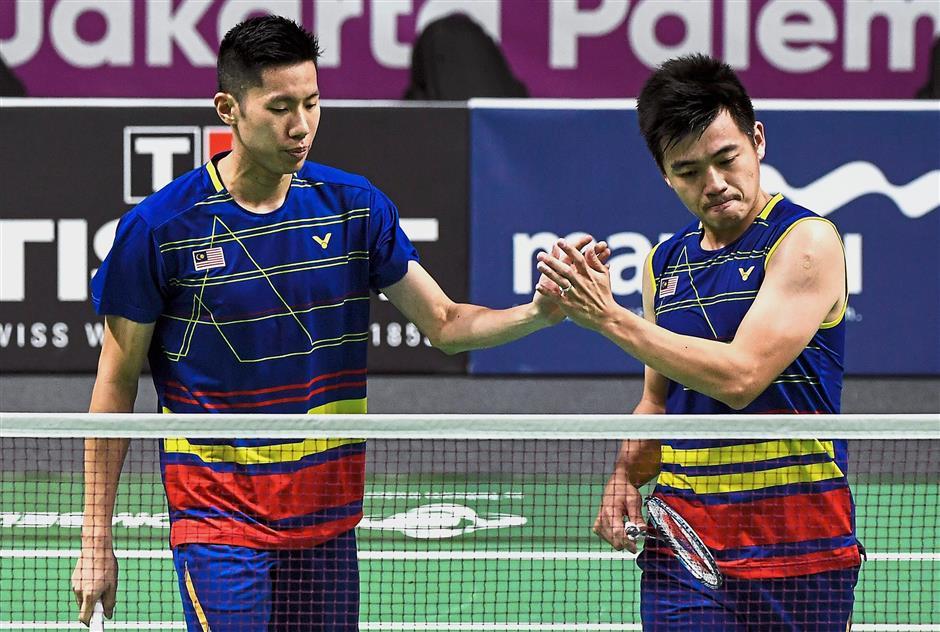 That was easy: Malaysiau2019s Goh V Shem (left) and Tan Wee Kiong celebrate after beating Thailandu2019s Kittinupong Kedren-Dechapol Puavaranukroh 21-15, 21-16 in the menu2019s doubles event yesterday. u2014 Bernama