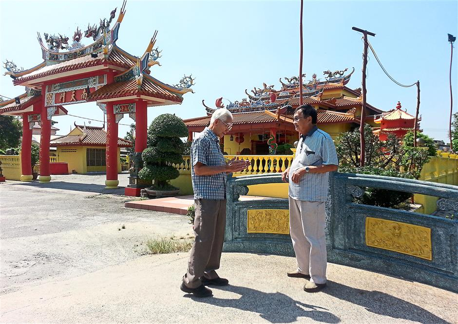 Reminiscing: Lee (right) having a chat with Yap outside the Nan Tian Gong temple in the village.