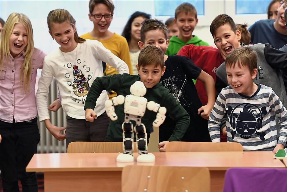 These youngsters clearly impressed by the talkative Robi, try to mimic the robots pose.