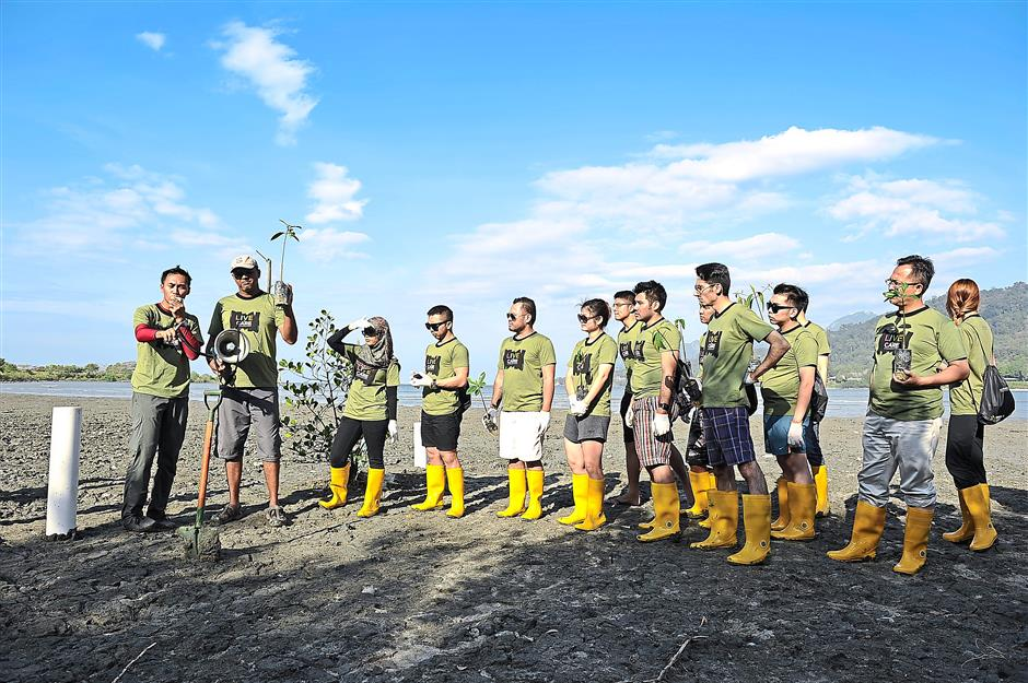 Step-by-step instructions: Media members, clad in yellow boots, listening to a briefing by Malaysian Nature Society personnel on how to plant mangrove saplings.