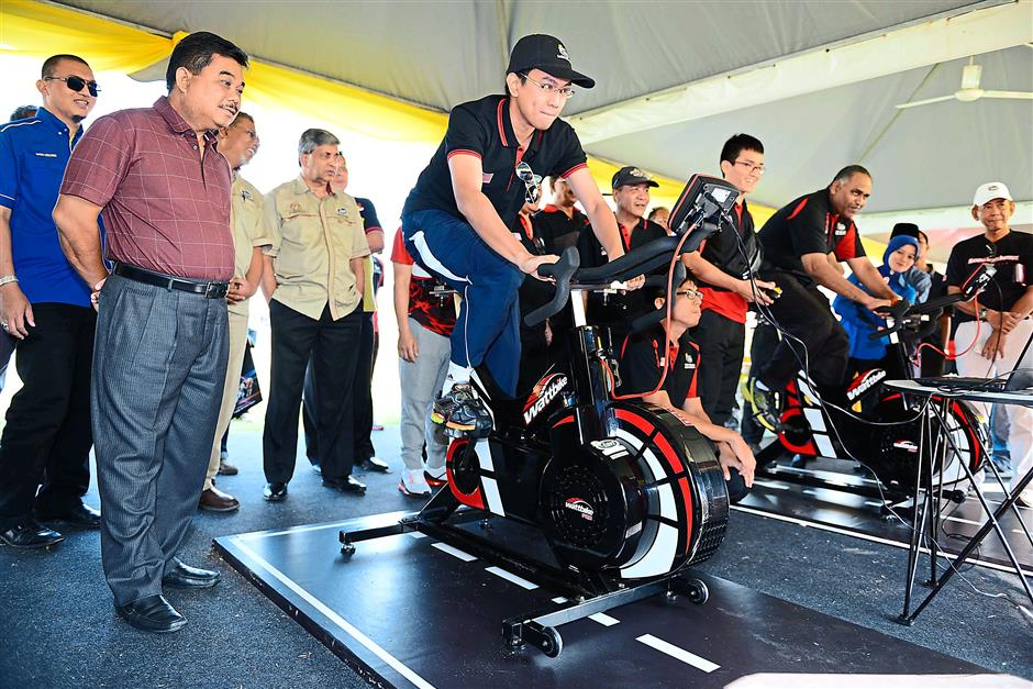Keeping fit: Tunku Zain (with cap) and Ramesh (second from right) trying the gym equipment at the launch of the programme.