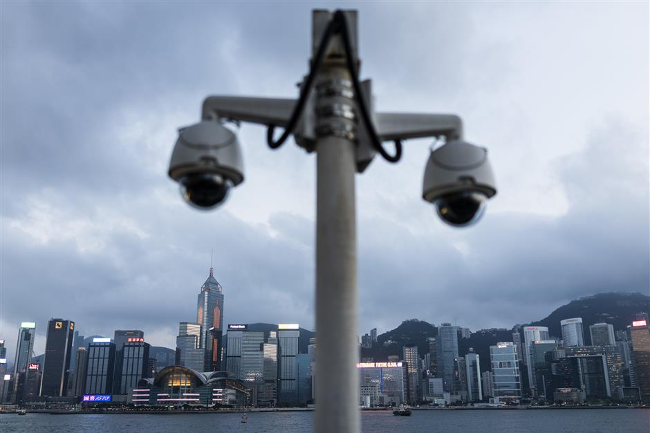 Surveillance cameras stand along Victoria Harbour in the Tsim Sha Tsui district as the Central Plaza plaza, center left, and other buildings on Hong Kong island stand in Hong Kong, China, on Monday, April 29, 2019. Hong Kong's gross domestic product will expand at a slower pace in the first quarter than the fourth because of the high base in the first three months of last year and due to external uncertainties, according to the city's financial secretary on April 28. Photographer: Justin Chin/Bloomberg
