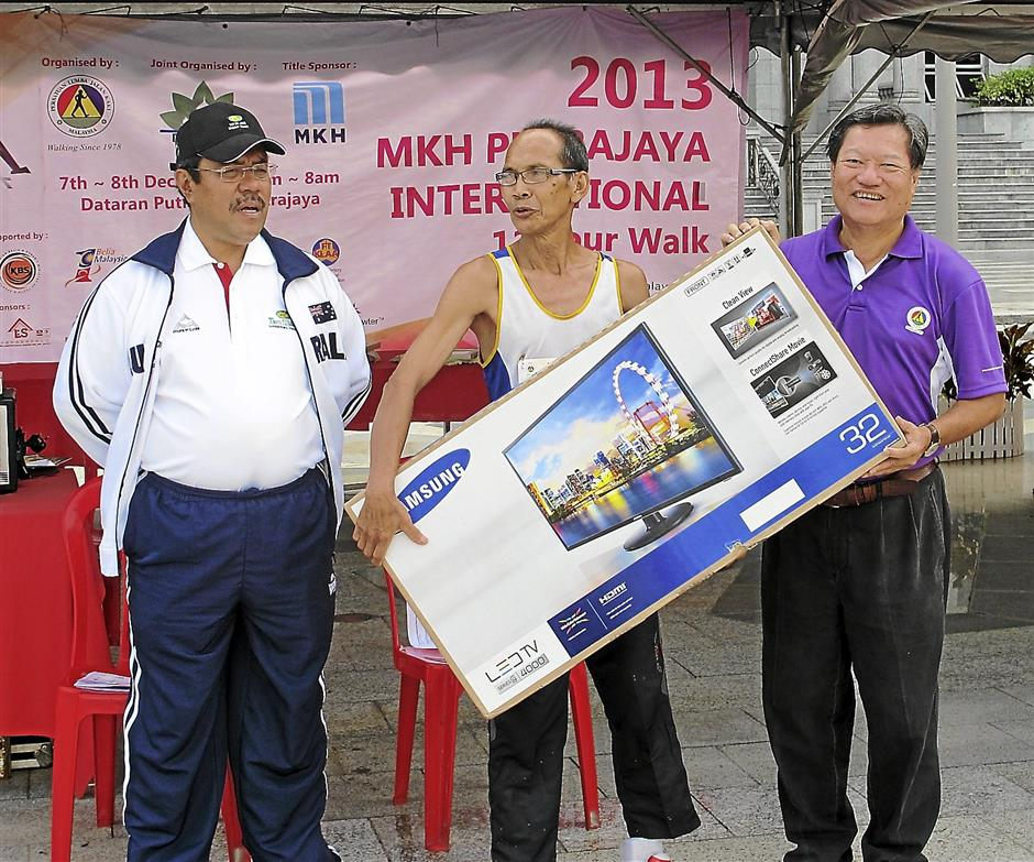 Lucky winner: Abdul Wahid Kassim (centre) receiving his prize from Tan Sri Eddy Chen (right) and Tan Sri Aseh Che Mat.