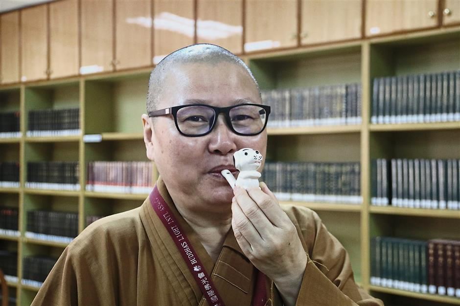 Ven Jue Cheng blowing a whistle in the shape of a dog, which is among the temple's canine figurine collection that serves as a reference and inspiration for the lantern-making team.