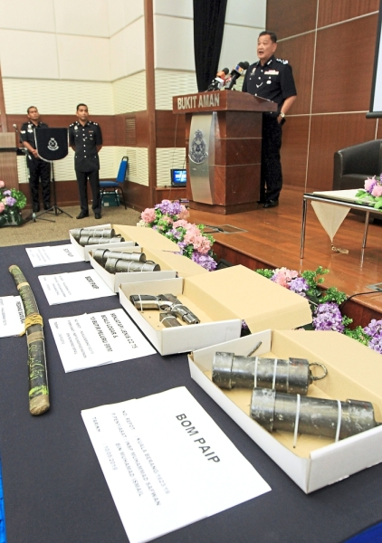 Swift action: Abdul Hamid addressing the media at a press conference with the weapons and explosives seized from the terrorists.