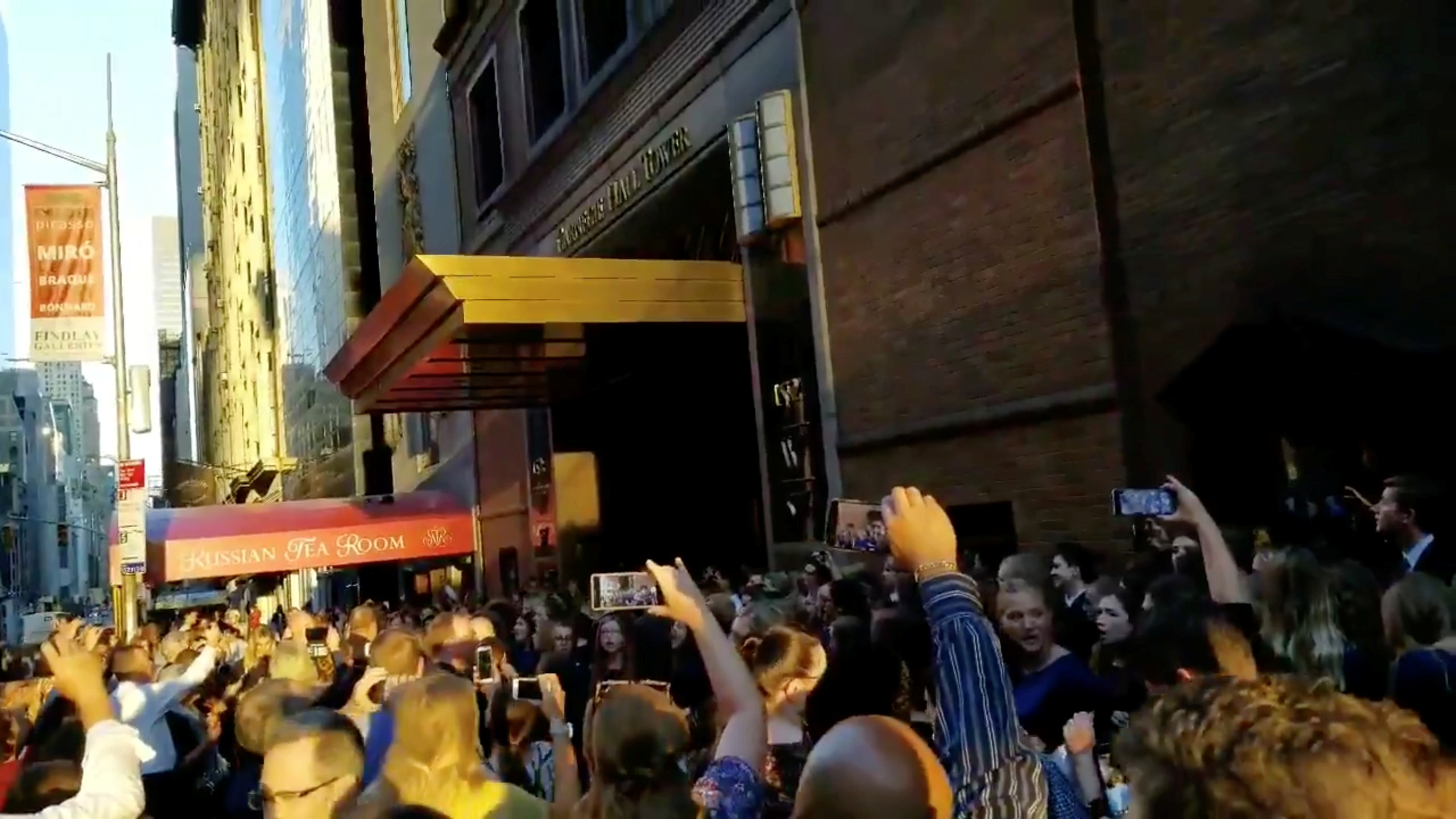 People evacuated from a Carnegie Hall concert during a blackout due to widespread power outages in the Manhattan borough of New York City, U.S, listen to the choir singing on the street in this still frame obtained via social media video July 13, 2019.  @MARLINPIE via REUTERS