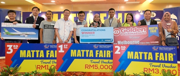 Tan (fourth from left) in a group photograph with the winners and sponsors of the MATTA Fair March 2019 Buyersu2019 Contest prize presentation.