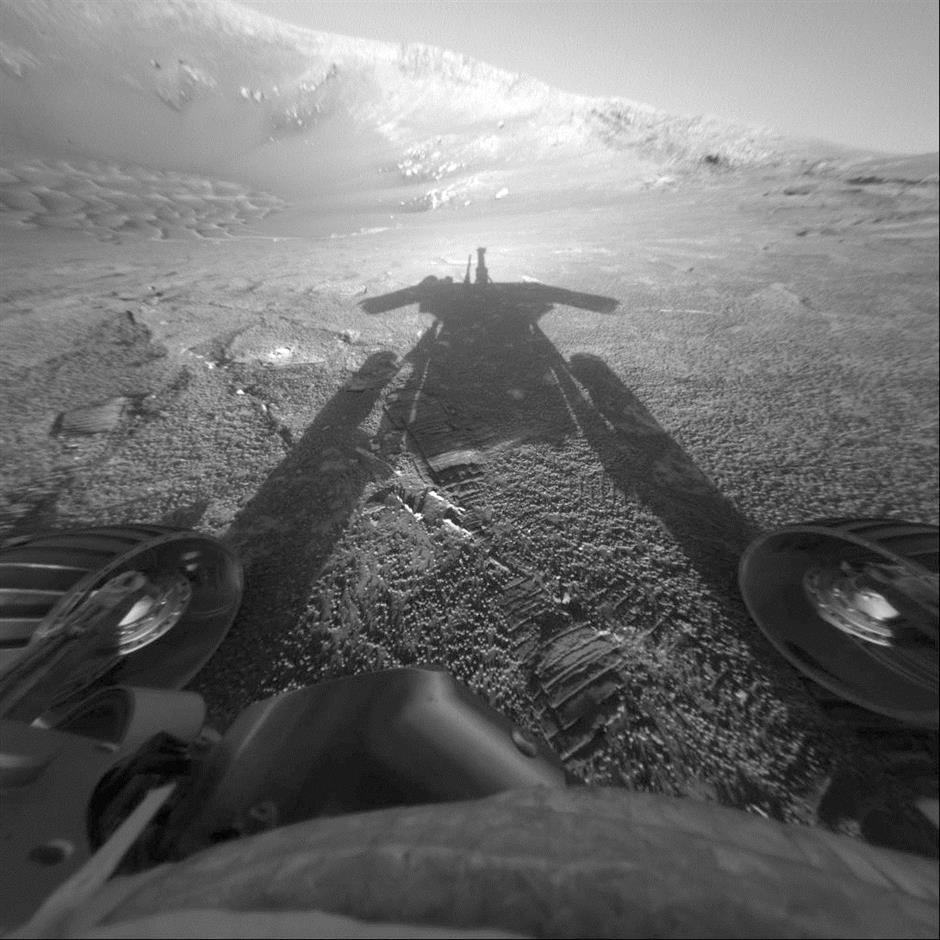 FILE - This July 26, 2004 file photo made available by NASA shows the shadow of the Mars Exploration Rover Opportunity as it traveled farther into Endurance Crater in the Meridiani Planum region of Mars. People took to social media this year to say goodbye to the Mars Opportunity rover when NASA lost contact on June 10, 2018, with the 15-year-old robot. (NASA/JPL-Caltech via AP, File)
