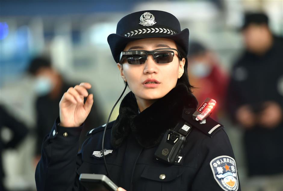 This photo taken on February 5, 2018 shows a police officer wearing a pair of smartglasses with a facial recognition system at Zhengzhou East Railway Station in Zhengzhou in China\'s central Henan province. Chinese police are sporting high-tech sunglasses that can spot suspects in a crowded train station, the newest use of facial recognition that has drawn concerns among human rights groups. / AFP PHOTO / - / China OUT
