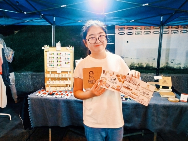Kelly showing the postcards and personalised book she bought at the bazaar. (Right) Wong showing some of the colourful stones with meaningful messages sold at her stall.