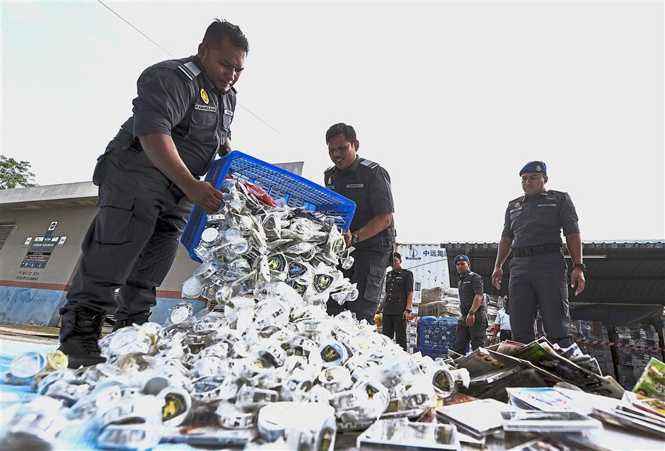 NILAI, 23 Jan -- Pegawai Penguatkuasa Kementerian Perdagangan Dalam Negeri, Koperasi Dan Kepenggunaan (KPDNKK) menimbus barangan rampasan untuk dilupuskan pada Program Pelupusan Ekshibit KPDNKK di Kompleks Penyimpanan Bahagian Penguatkuasa, KPDNKK di Arab Malaysian Industrial Park hari ini.Pelupusan barangan rampasan sepanjang 2017 dan Januari 2018 melibatkan 368 kes di bawah pelbagai akta antaranya Akta Hakcipta 1987, Akta Prihal Dagangan 2011, Akta Juala Langsung dan Skim Anti Piramid 1999, Akta Cakera Optik 2000 dan Akta Perlindungan Pengguna 1999 dengan nilai barangan rampasan sejumlah kira-kira RM6.87 juta membabitkan barangan rampasan seperti VCD, DVD, kasut, pakaian, toner, arak, barangan elektrik, mesin pengilangan dan kelengkapan dapur.-- fotoBERNAMA (2018) HAK CIPTA TERPELIHARA