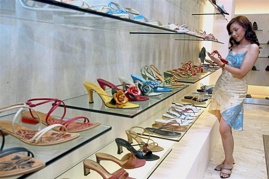 In different hands: A customer checking out Lewre shoes. The retail business is now taken over by Lew's daughter.