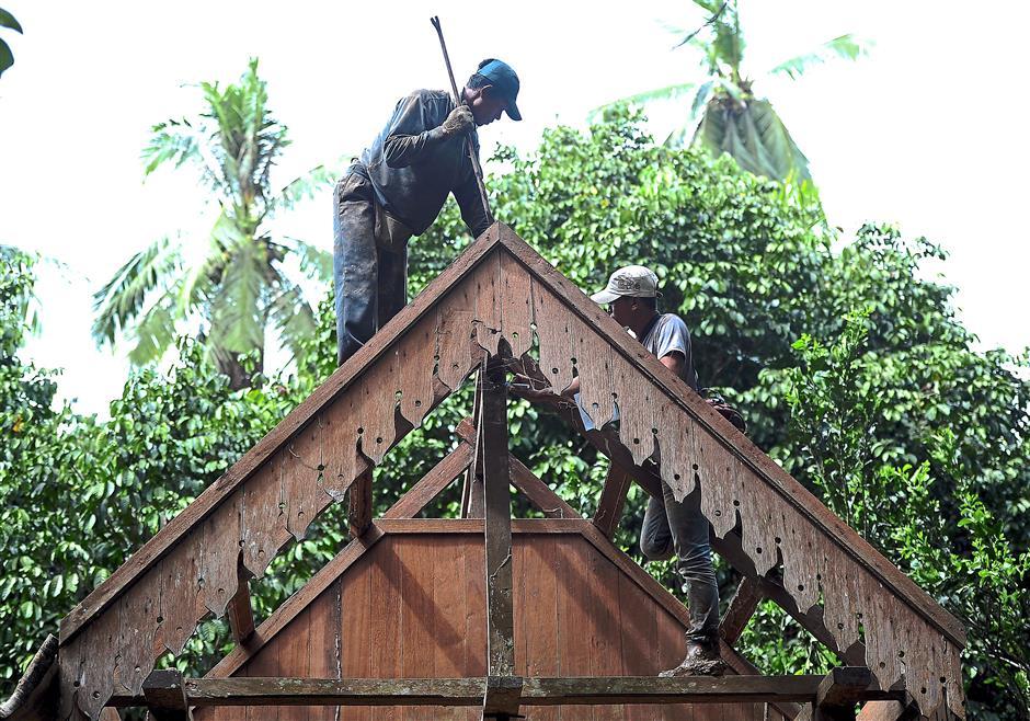 In the name of preservation: Museum workers dismantling the roof on-site in Kampung Kelola, Jerantut last month. – Bernama
