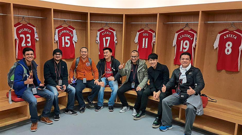 Happy lads: (from left) Vishaan, the writer, Danny, Lenny, Hway, Joseph and Paul in the Arsenal dressing room during the tour of the Emirates stadium.