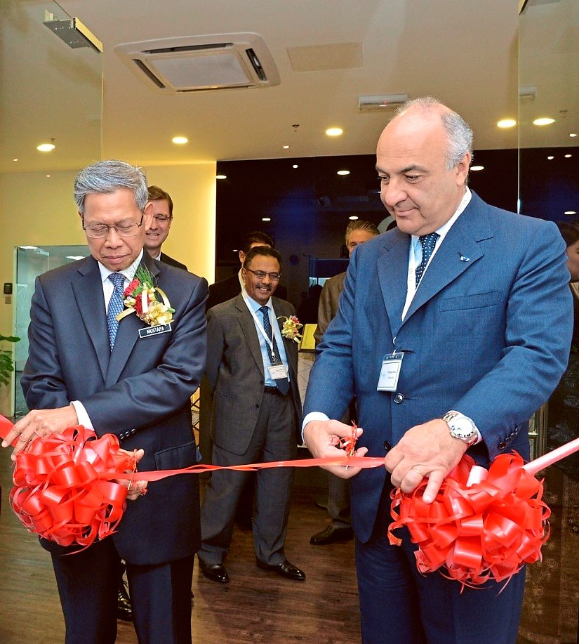 Ready to operate: Mustapa and Amon cutting the ribbon at the opening of the RM5mil Sicpa Asia Pacific Centre.