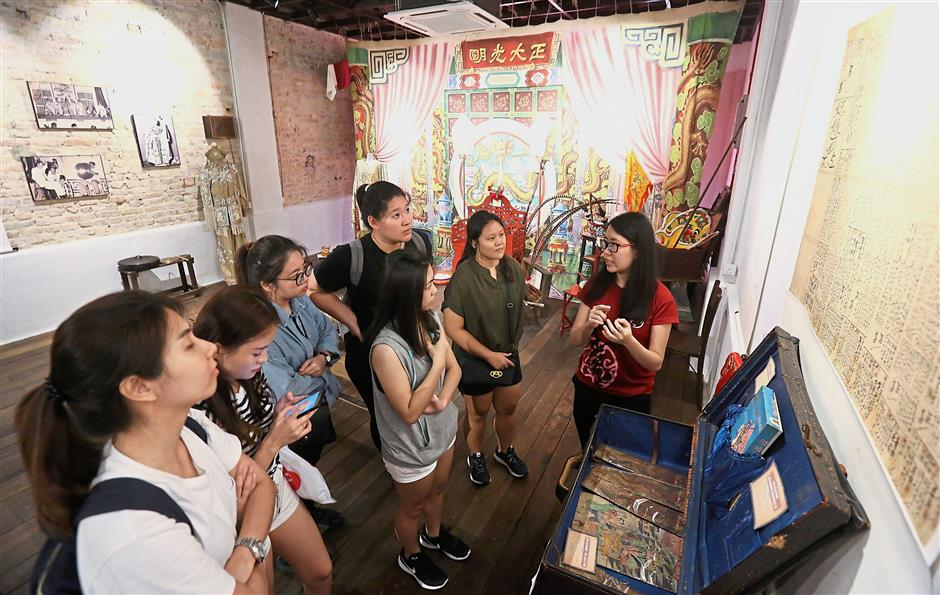 A guide (right) explaining to visitors the development of Chinatown's theatre scene at Petaling Street Heritage House. The centre is in urgent need of volunteers as guides, writers or translators. — Photos: AZHAR MAHFOF/The Star
