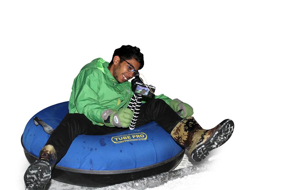 Abram smiles into his smartphone as he records his snow tubing ride.