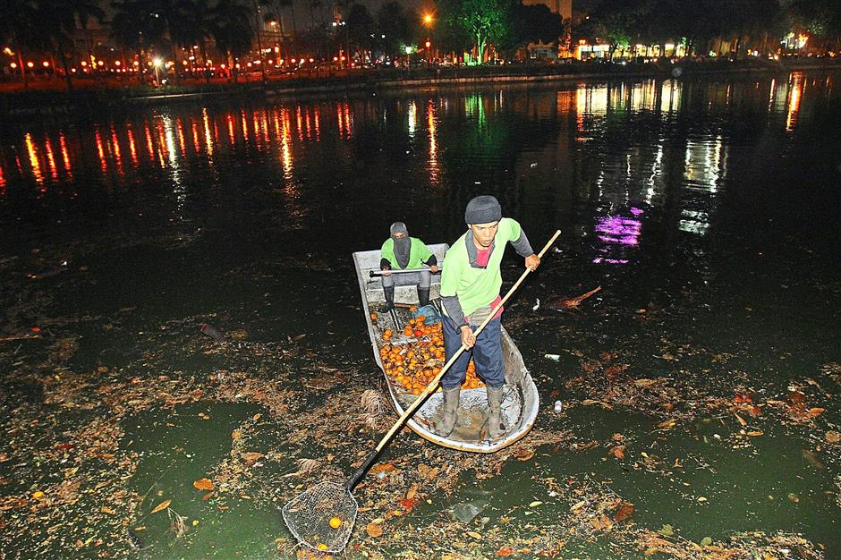 The clean up crew of the lake helping to retrieve the oranges that floated beyond the reach of visitors in Tasik Taman Jaya at the 2014 Chap Goh Meh celebrations.