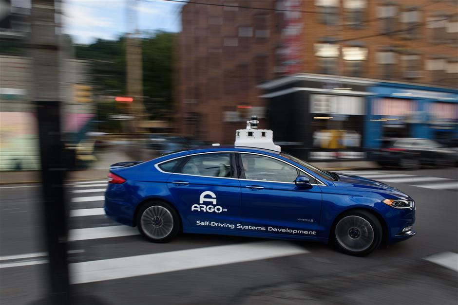 An Argo AI modified Ford Motor Co. Fusion autonomous vehicle is seen driving along a street near the company\'s headquarters in Pittsburgh, Pennsylvania, U.S., on Thursday, Aug. 16, 2018. The investment in Argo AI, a self-driving startup, is Ford\'s way of trying to catch up to Alphabet Inc.\'s Waymo and General Motors Co. in the driverless derby. Ford took a majority stake in Argo last year and expects to deploy autonomous vehicles running its system in a money-making business by 2021. Photographer: Justin Merriman/Bloomberg