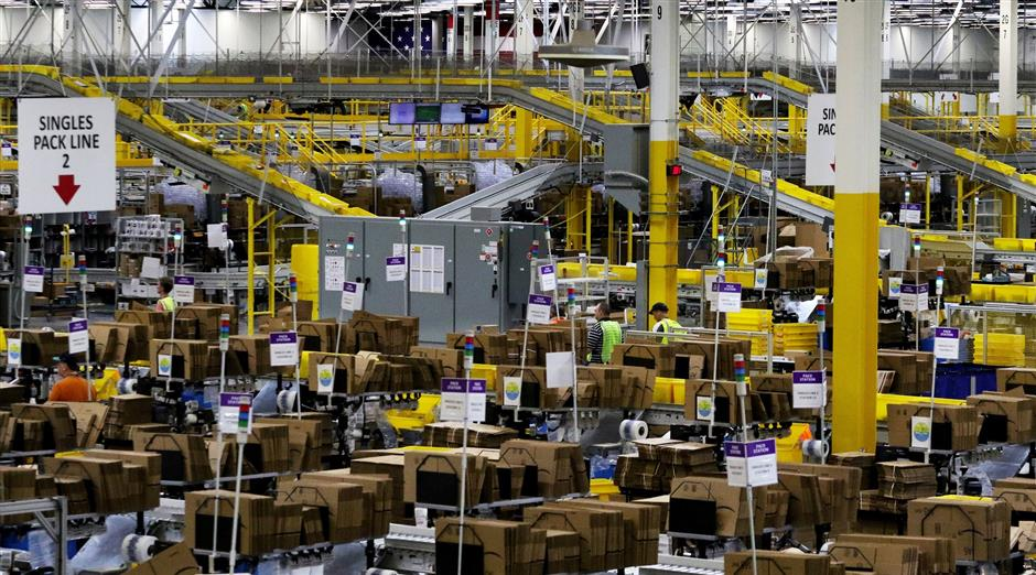 The warehouse floor is filled with the sound of machinery, although the robotic storage pods move almost silently. Overhead, conveyors move yellow totes with more goods. (Alan Berner/The Seattle Times/TNS)