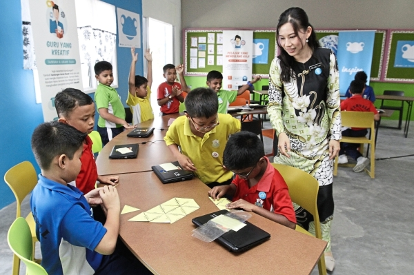 English teacher Ong Hwee Fung teaching a Year Three class the topic on Occupations with the pupils taking an online quiz on Boost sites and completing a group puzzle activity.