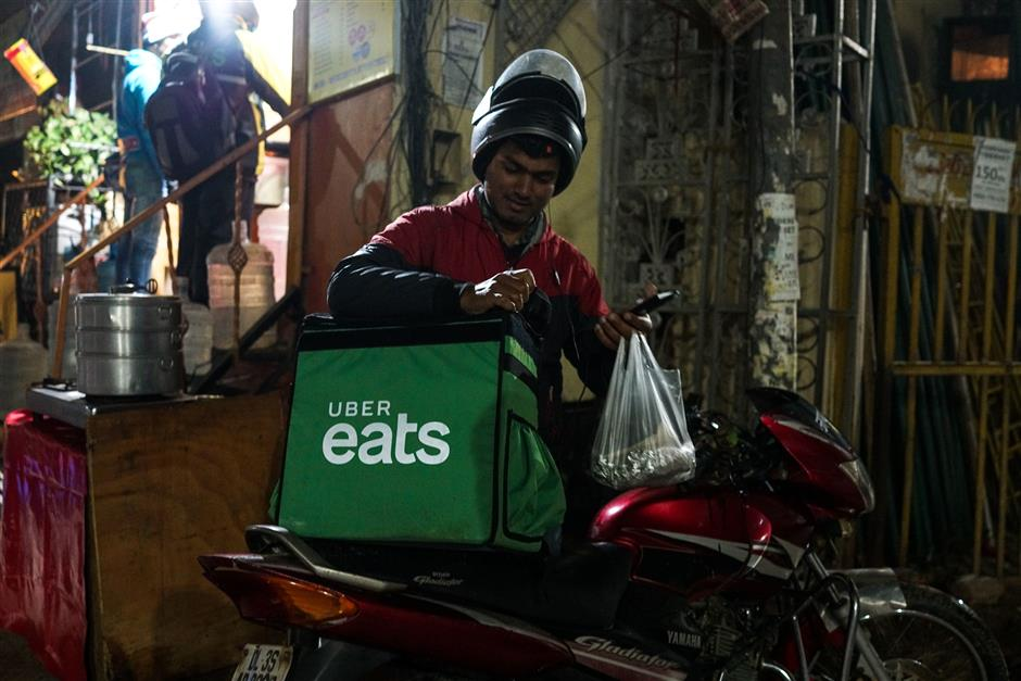 In this photograph taken on February 6, 2019, an Indian delivery man working with the Uber Eats food delivery app loads up food to bring to a customer in New Delhi. - A surge in the popularity of food-ordering apps like Uber Eats, Swiggy and Zomato provides a welcome source of income for many as India's unemployment rate sits reportedly at a staggering 45-year high. (Photo by CHANDAN KHANNA / AFP) / To go with 'INDIA-ECONOMY-FOOD-TECHNOLOGY,FOCUS' by Vishal MANVE