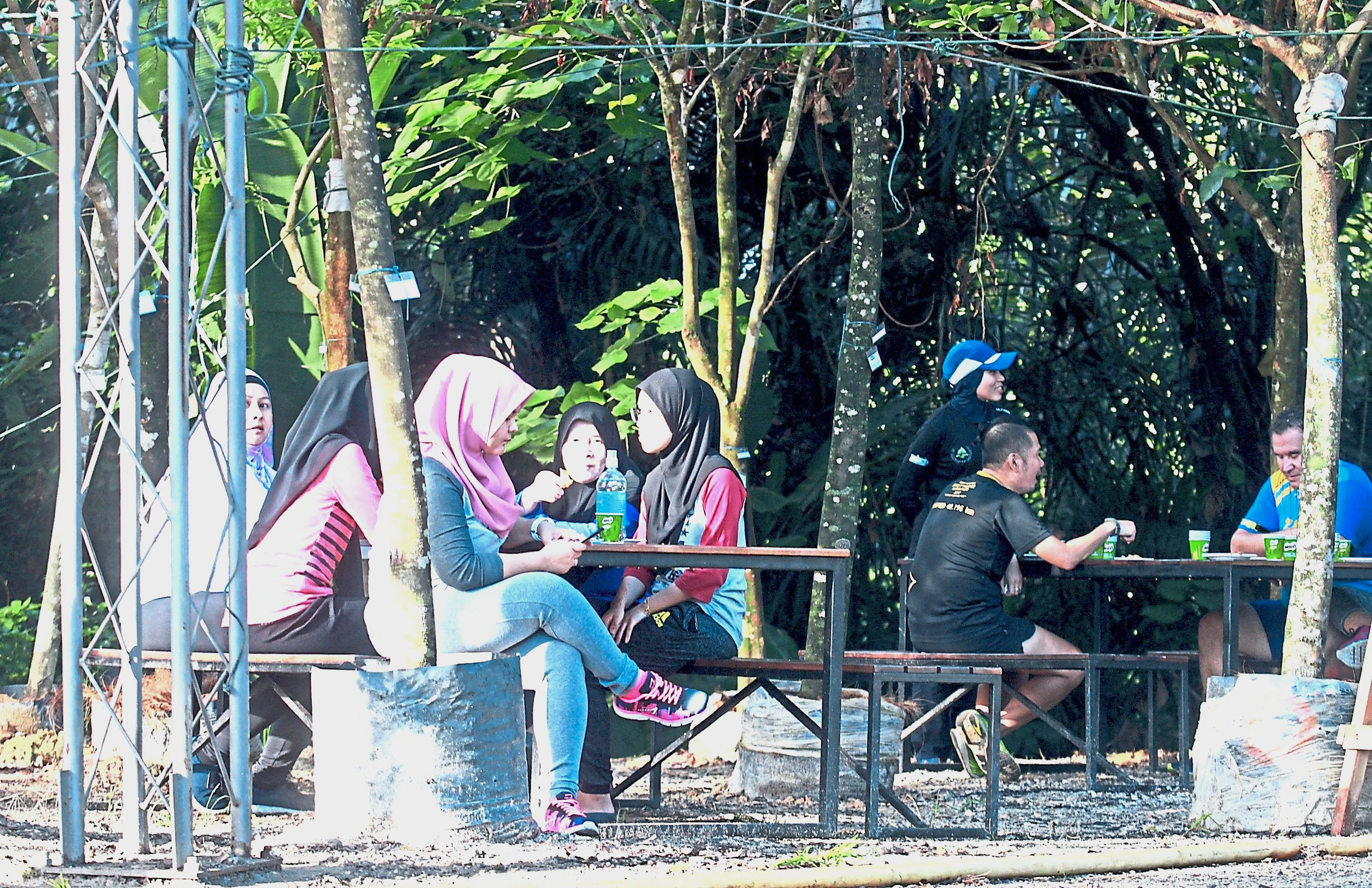 A group of visitors chilling out under the green canopy of Taman Tugu.