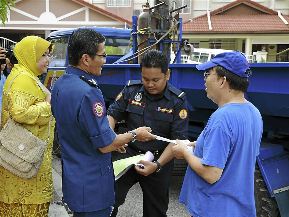 MBPJ enforcement officers handing over a notification slip to Winchester Ara Damansara RA member Say, informing him that he could retrieve the cut-up wheeled gate from the council within a period of 14 days.