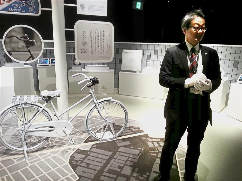 Ishida showing the bullet-shaped bicycle lamp Matsushita made that proved to be hugely popular as it could last 10 hours longer than the competition.