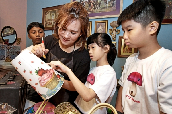 Wong teaching students the decoupage technique of decorating a wooden plaque. (Left) Students glueing decorative elements onto key boxes.