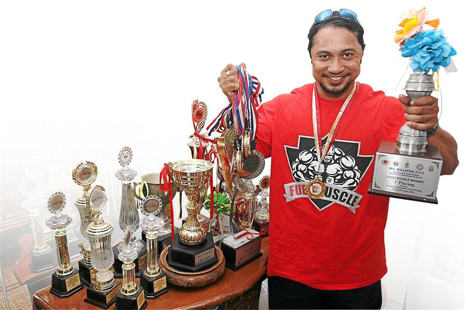 Badrul Shah Baharuddin showing his coveted Mr Malaysia champion trophy and many bodybuilding medals at his home in Kuala Lumpur.