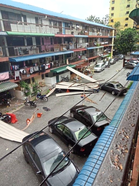 Roofs ripped off: Zinc sheets scattered after the storm at  the UDA flats near Tanjung Tokong.