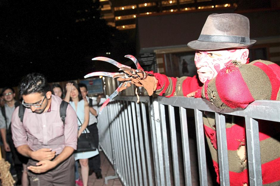 An actor dressed as Freddy Krueger from the popular horror film, 'A Nightmare on Elm Street', reaching over the fence as guests queue up outside one of the attractions.