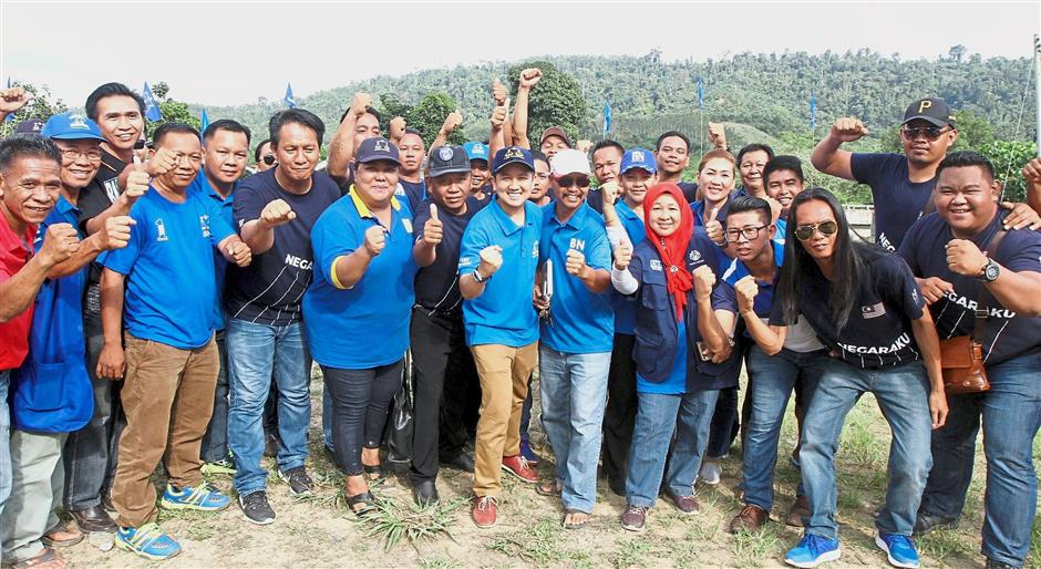 Thumbs up: Arthur (centre, wearing dark blue cap) posing for a group photo with locals during his campaign trail in Sook.