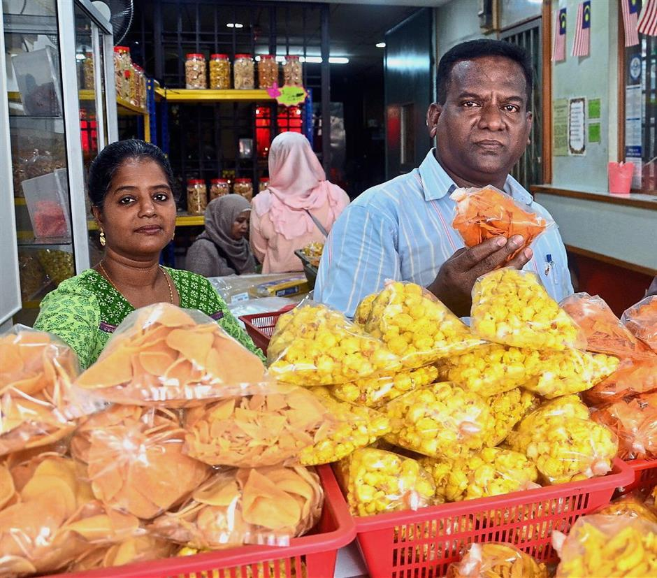 Thanaveeran (right) and his sister-in-law B. Diwi manning their titbits kiosk in Jalan Dhoby.