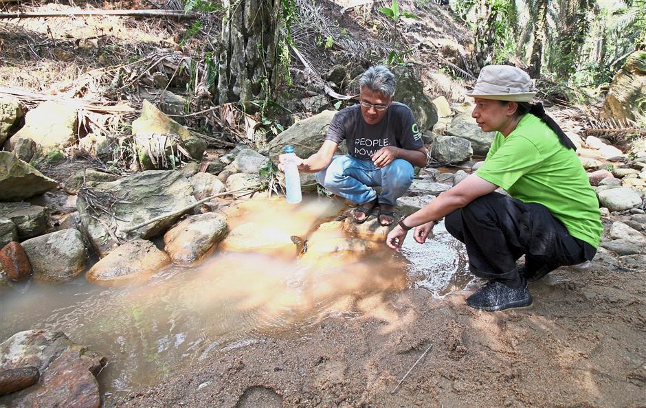 Meor Razak (left) and Sajeeda showing the murky water of Sungai Kepar. — Photos: SAIFUL BAHRI/The Star