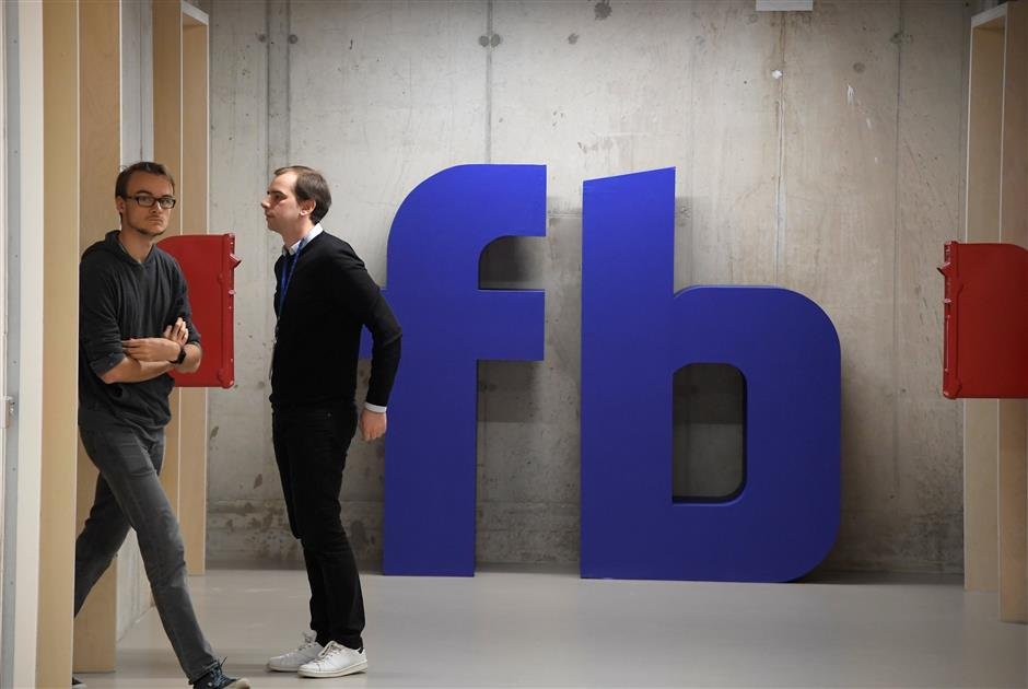 A man waits for an elevator in front of a logo at Facebook\'s headquarters in London, Britain, December 4, 2017. REUTERS/Toby Melville
