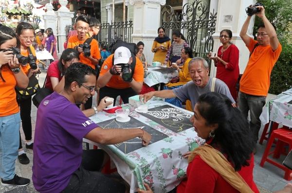 Different patterns: Visitors enjoying doing Kolam at  the Penang Hindu Association booth during the event. — ZHAFARAN NASIB/The Star