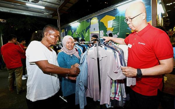 Doing the needful: Chan (right) and Dr Rusaslina helping former driver Jalaludin choose clothes at Kedai Jalanan.