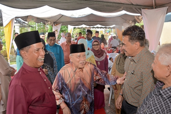 Mohamed Fadzill (left) welcoming Abdul Rahman to his open house.