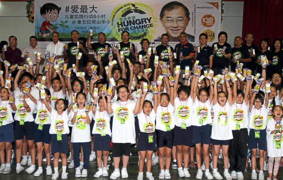 The children of SJK Bukit Merah in Lahat cheering with joy as they hold up the food and packet drink they received.