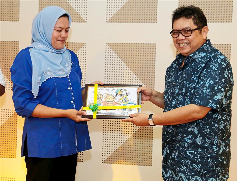 """State Health, Tourism and Culture Committee chairman Nolee Ashilin (left) presenting a souvenir to Datuk """"Lat"""" Mohd Nor Khalid during the opening ceremony of Kaki Kartun Carnival at Kellie's Castle."""