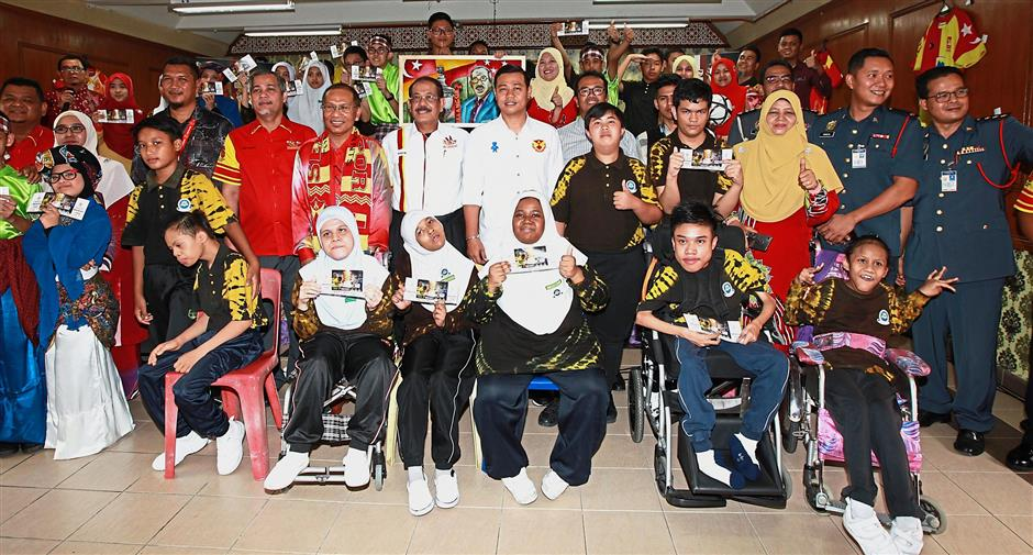 A group shot of the students with the TSSC committee members. A total 36 students from SMK Seri Keramat's Special Needs Integration Programme (PPKI) will get to enjoy this Saturday's matches alongside thousands of other football fans this Saturday. — NORAFIFI EHSAN/The Star