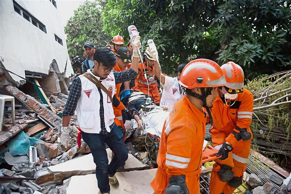 To safer ground: Rescue personnel evacuating a survivor from the rubble of a collapsed restaurant in Palu. — AFP