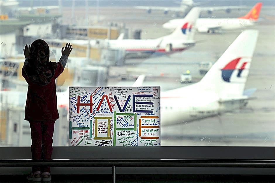 DO NOT USE ONLINE FOR PAGE 1Kids standing near the wishing message for the missing MAS flight MH370 at KLIA yesterday.AZMAN GHANI / The Star