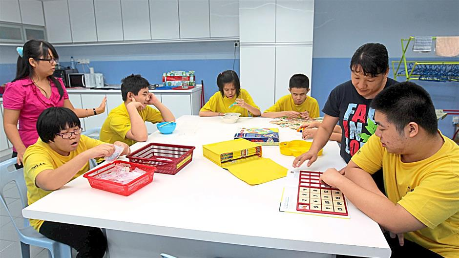 Thinking caps on: Special needs teens working on puzzles as their teachers watch them.