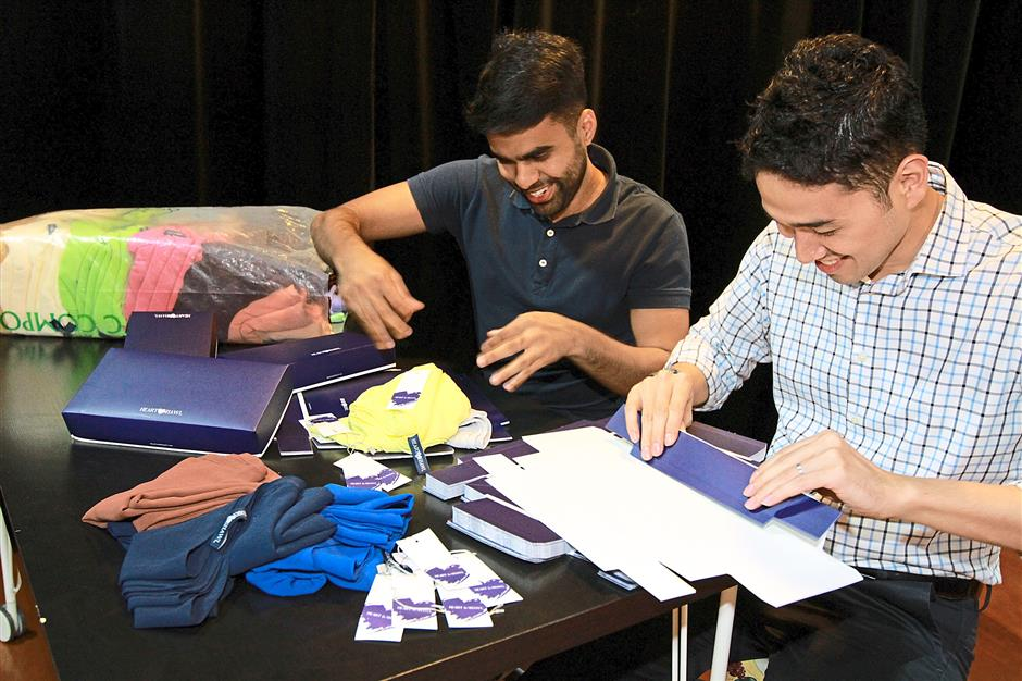 Kaiser (left) and Hafeez pack the shawls in custom-made boxes before they are sent out to customers who ordered online.