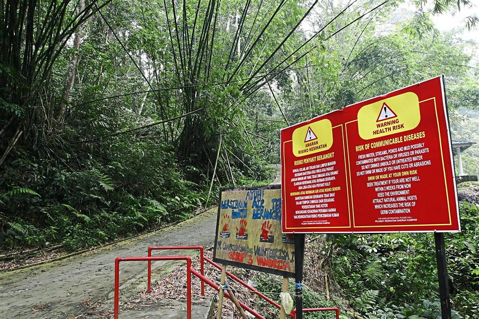 The Batu Berangkai waterfalls in Kampar with the signage of beware of health risk of communicable diseases.