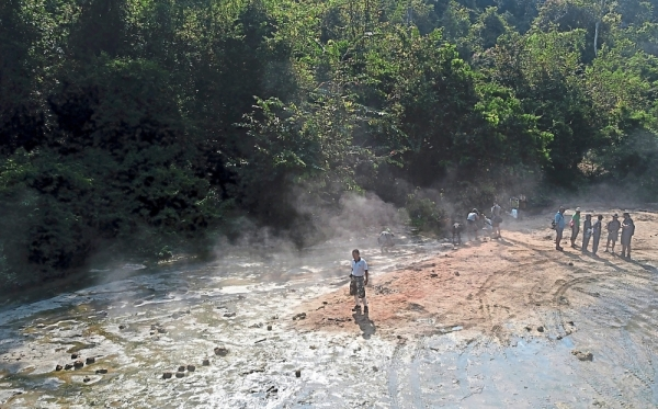Following the trail: Newsmen and environmentalists observing tyre tracks made by poachers at a hot spring in Ulu Muda Forest Reserve.